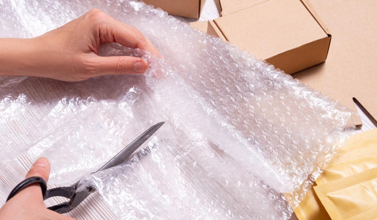mujer cortando película de burbujas para embalar envio